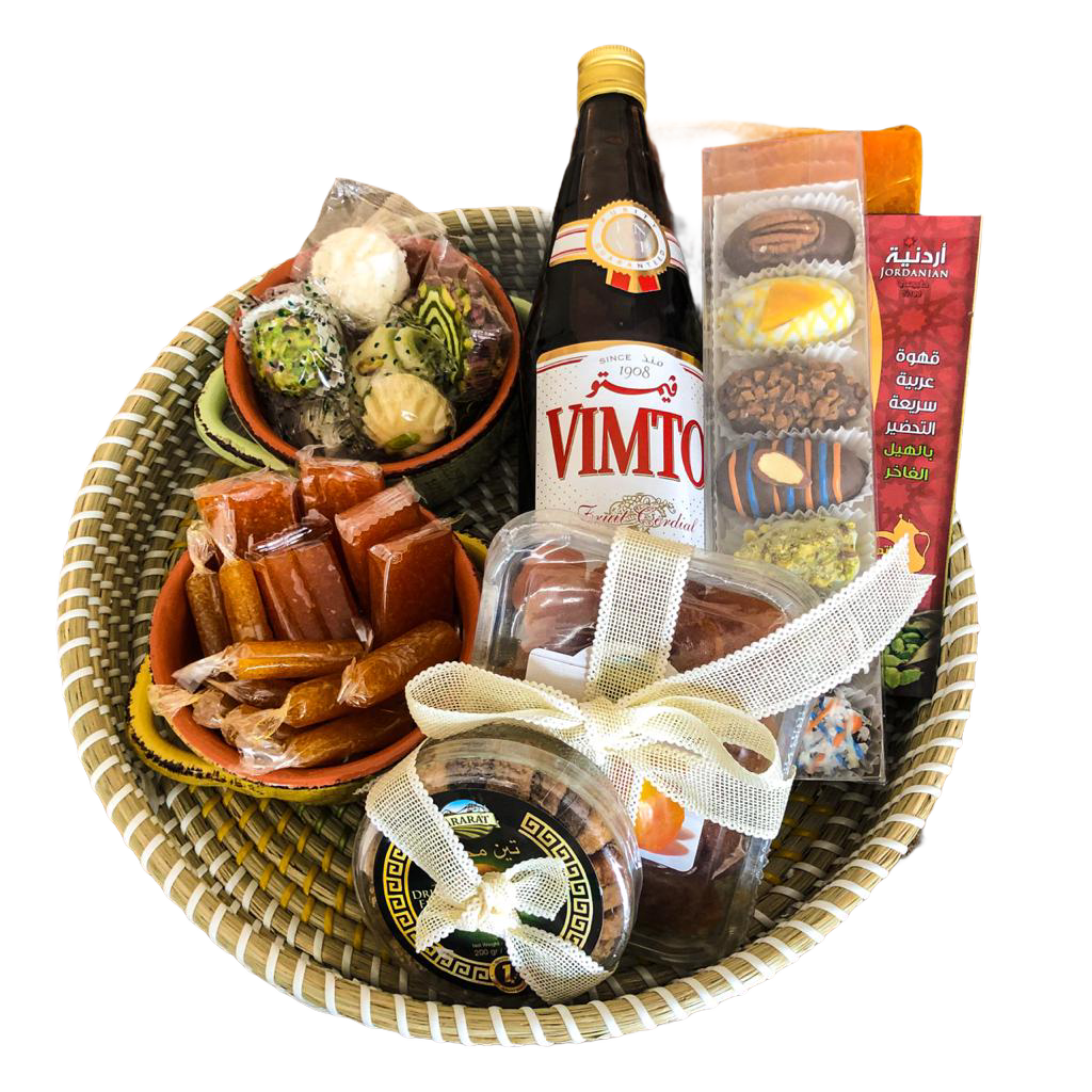 A Wicker Basket from Baskets containing Vimto, Chocolate covered dated, assorted sweets, ceramic plates