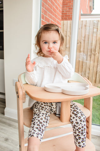 girl in wooden high chair