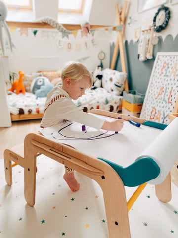 child drawing on desk