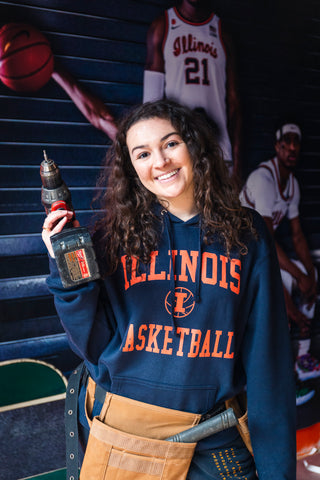 woman in illinois basketball hoodie holding a drill while building out an illinois basketball store in chicago