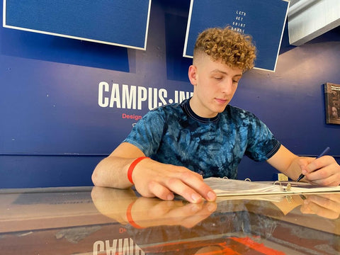 Pictured above, Podziemski signing at the Campus Ink Lab, Friday, July 9.