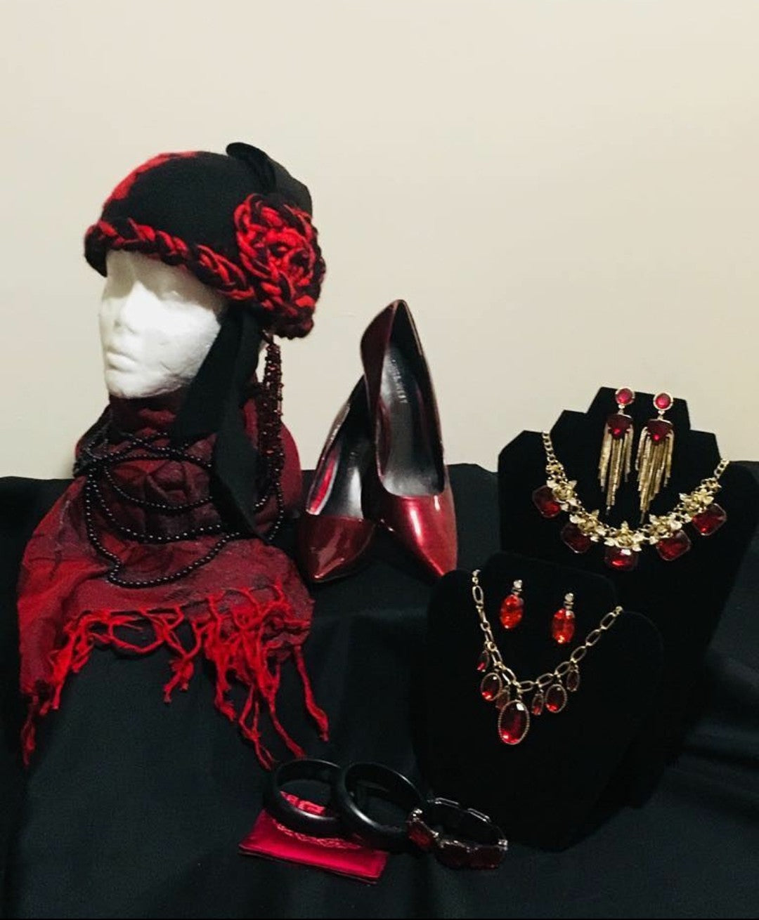 red and black felt cloche with bead tassel. Red stilettos, red rhinestone jewelry, and black bracelet and red cardholder