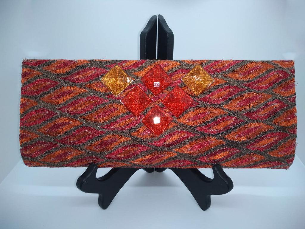 Orange clutch with square orange beads on stand
