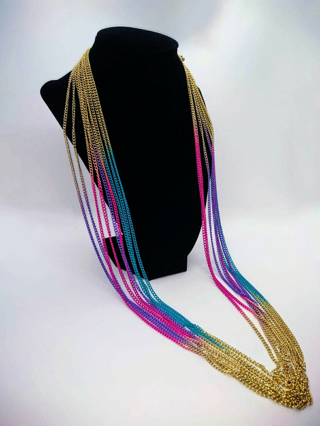 gold multi strand necklace with purple, turquoise, and pink accents draped on black stand