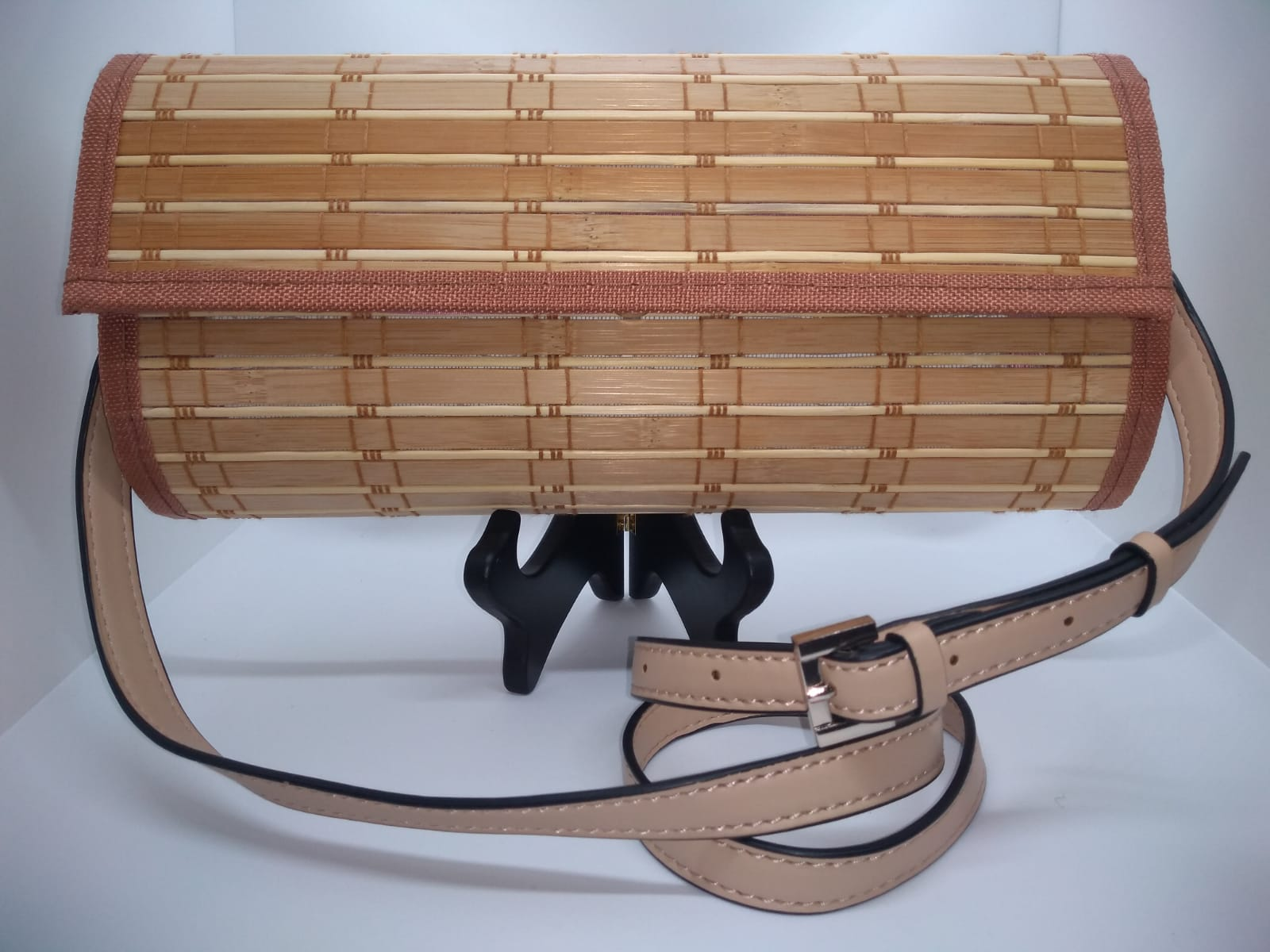 Nude colored wood crossbody handbag with beige pleather strap.