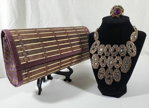 brown and purple wood clutch with brass and rhinestone chunky necklace on stand topped with beaded ring