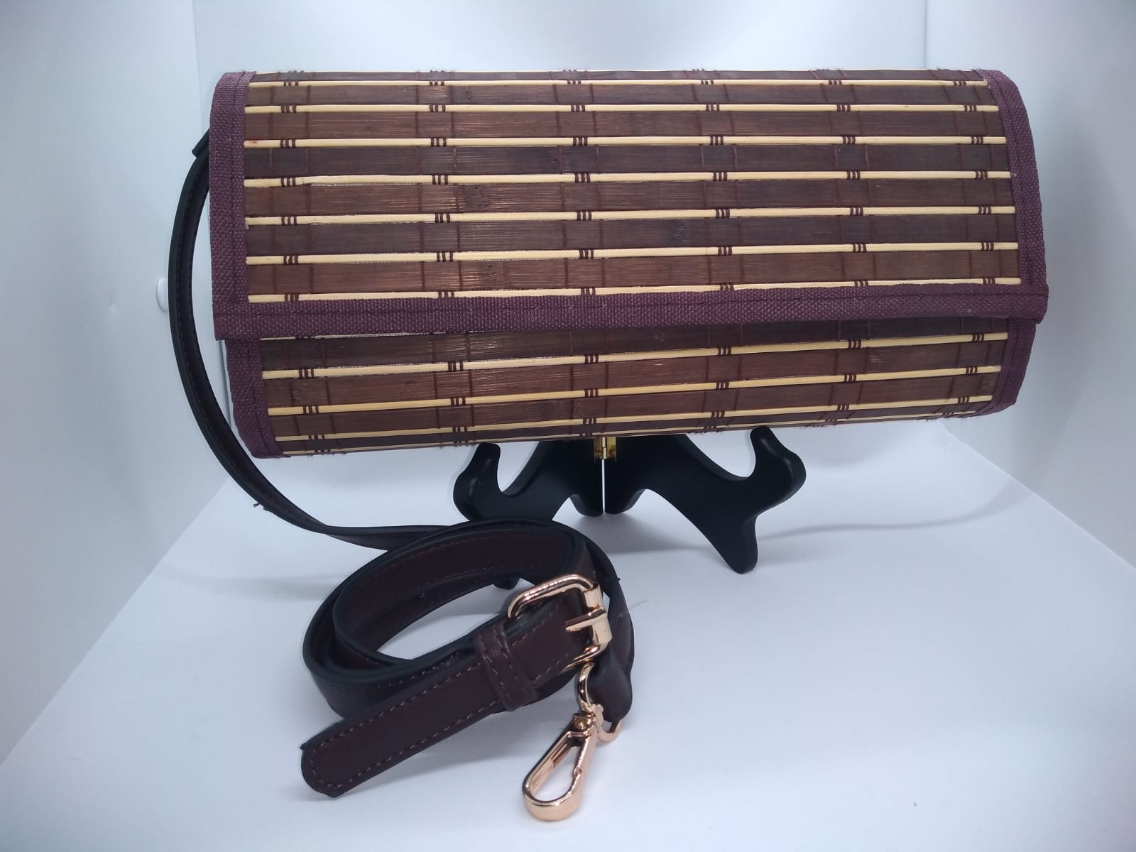 brown and purple clutch front view with deep brown shoulder strap with gold hardware.
