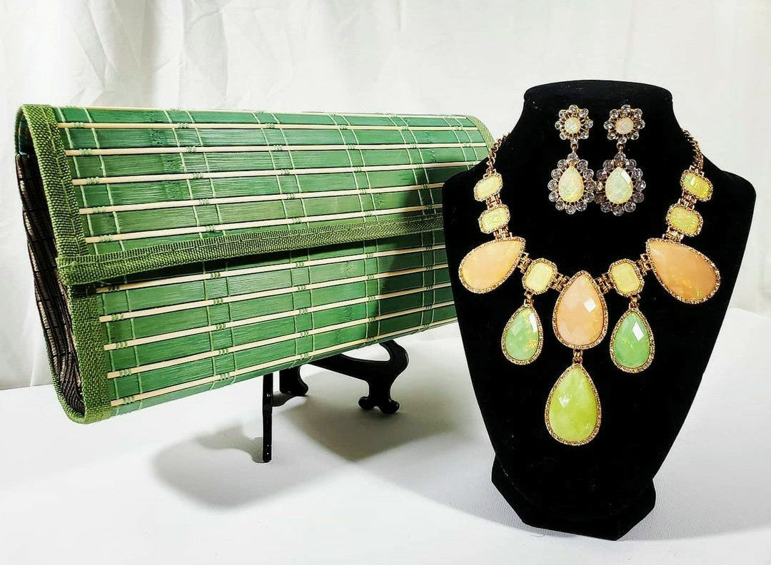 green wooden clutch beside citrus rhinestone chunky necklace and earring set on stand