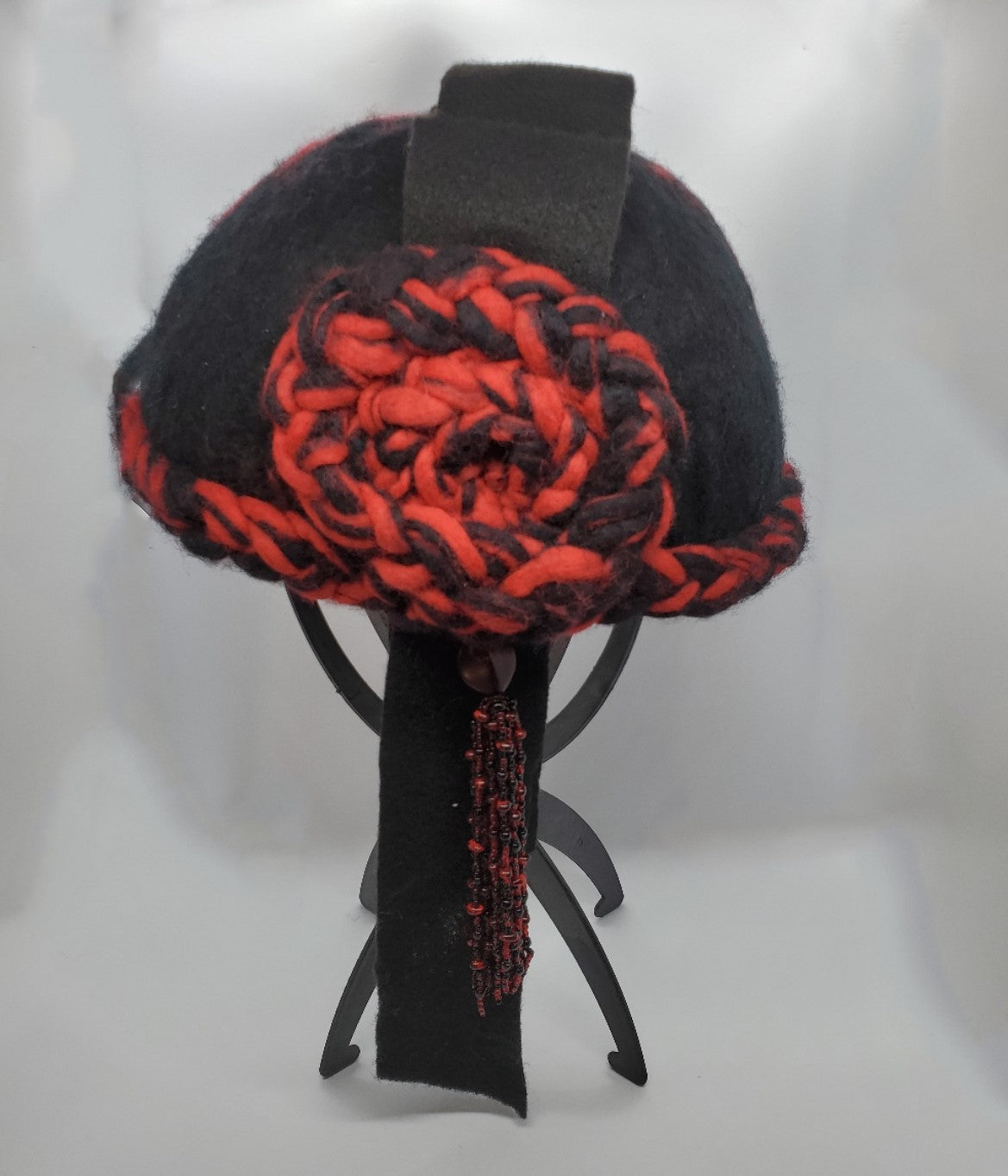felt cloche with beaded tassel in red and black on stand
