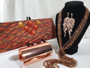 shimmery orange clutch with lasso bead necklace, rose gold rhinestone earrings on stand and copper cuff at forefront