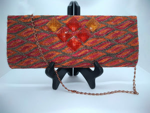 Orange clutch with chain strap and square orange beads on stand