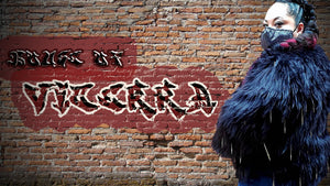 female model wearing black fur coat with chain tassels in front of a graffiti brick wall