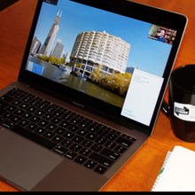 Load image into Gallery viewer, architecture virtual event on laptop with man narrator and coffee mug