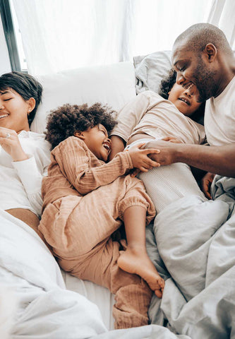 family smiling in bed - pexels - Rainbow Yoga Training