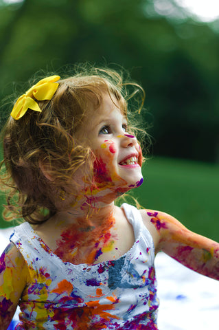 Smiling toddler with paint on face - Rainbow Yoga Training