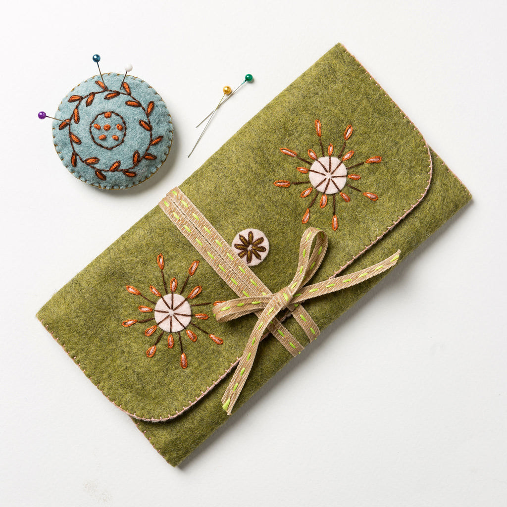 This Sewing Roll folds in three and is closed with a pretty saddle stitch ribbon. It has pockets for buttons, thread, a thimble and scissors, needles and tape holders and even a detachable pin cushion.