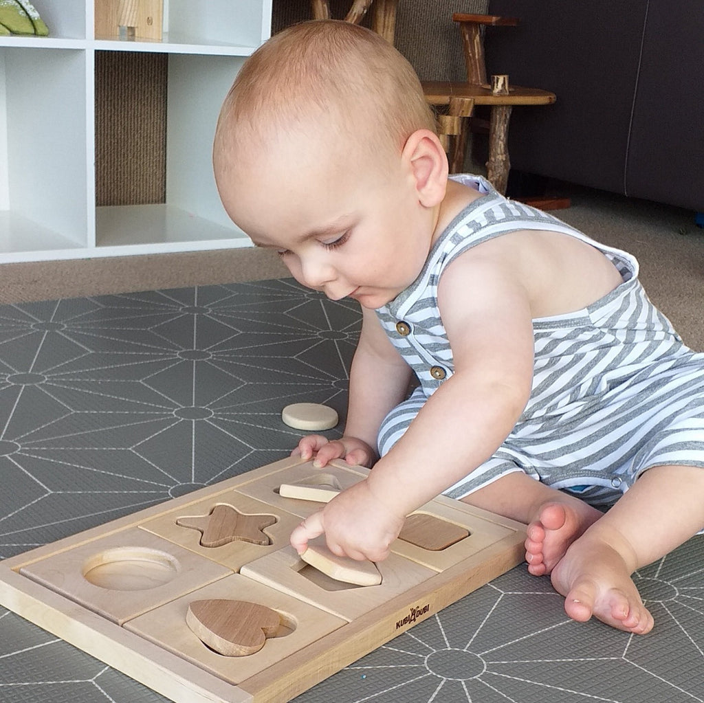 Toddler playing with Kubi Dubi shape sorting puzzle