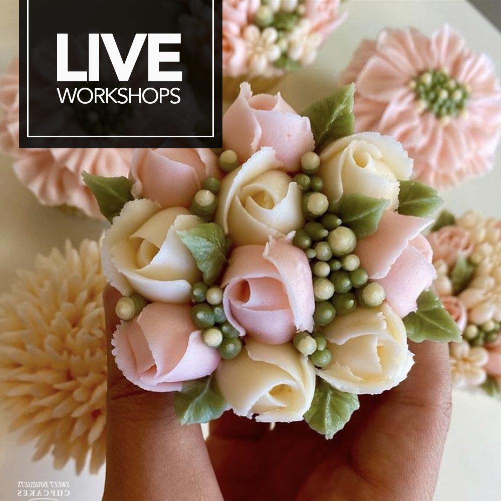 Woman using piping bag to ice a single tier large cake - LIVE Workshops.