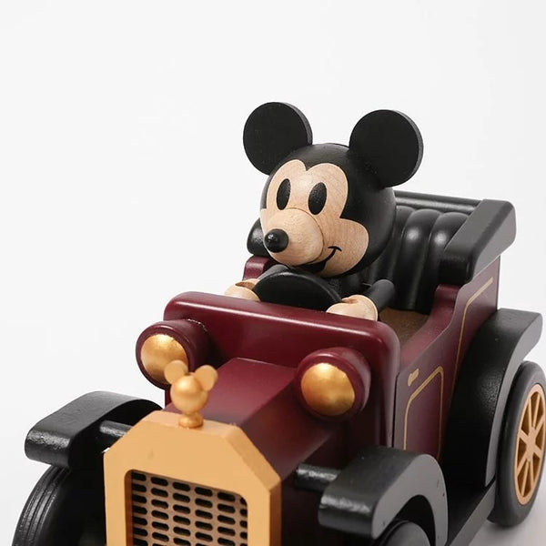 mickey smiling while driving a classic car