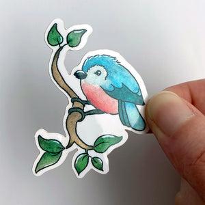 A vinyl sticker of an illustrated blue bird perched on a branch. This original watercolour and ink design is from the Found and Lost Art spring collection.