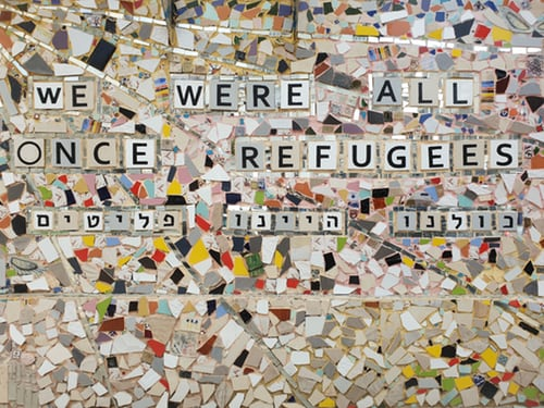 "alt=""we were all once refugees in English block letters and in Hebrew letters on mosaic stone pieces"""