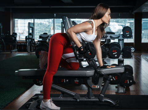 Women on bench lifting weights