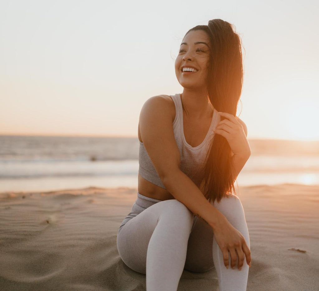 How to lose lower belly fat: Woman smiling on beach