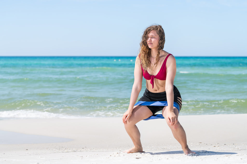 Woman doing squats on the beach