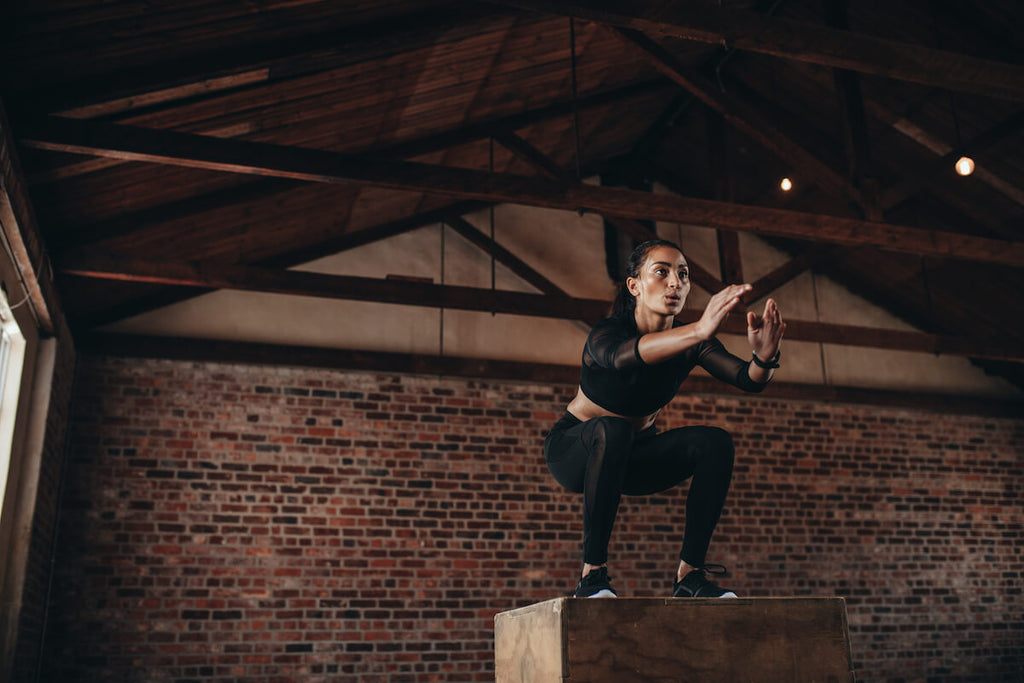 Metabolic workout for women: woman doing a box jump