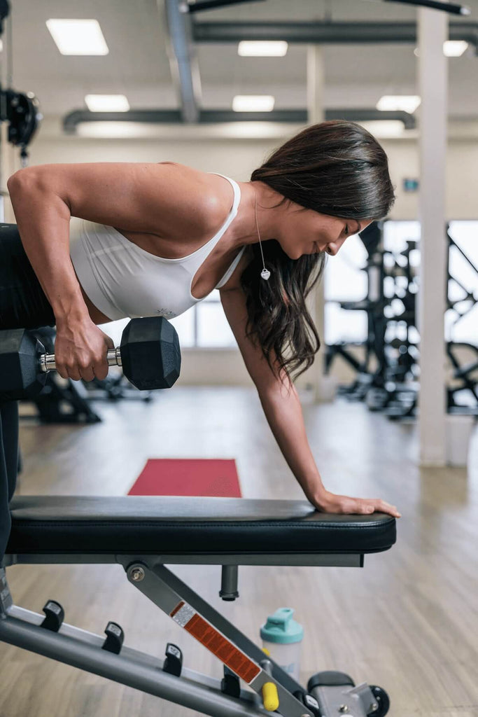 Woman doing dumbbell arm rows at the gym