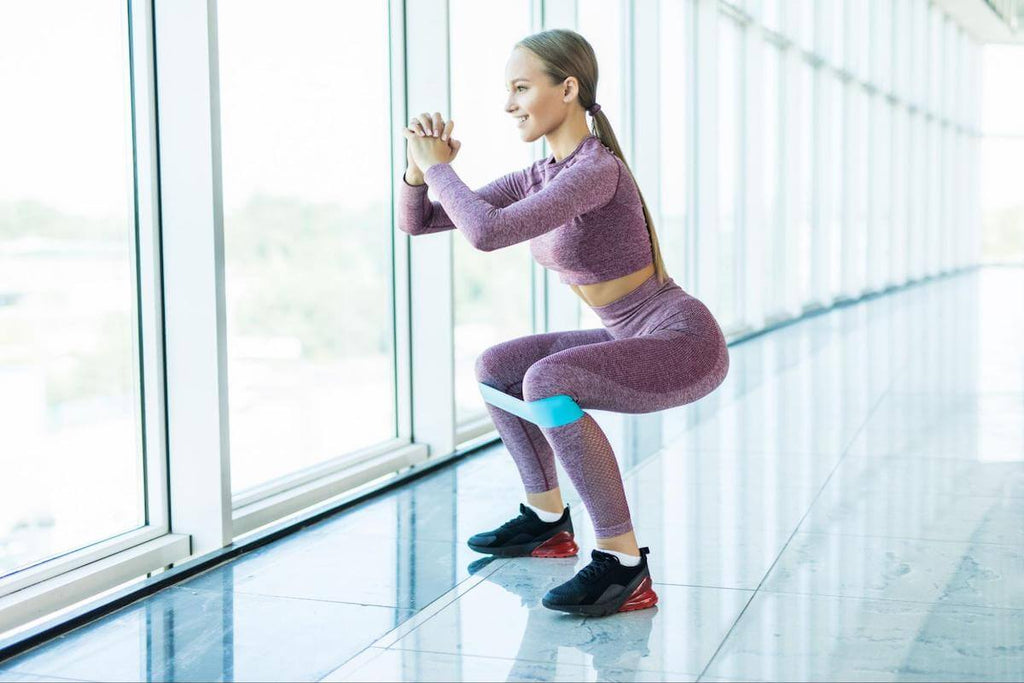 Woman doing crab walk exercises with a resistance band