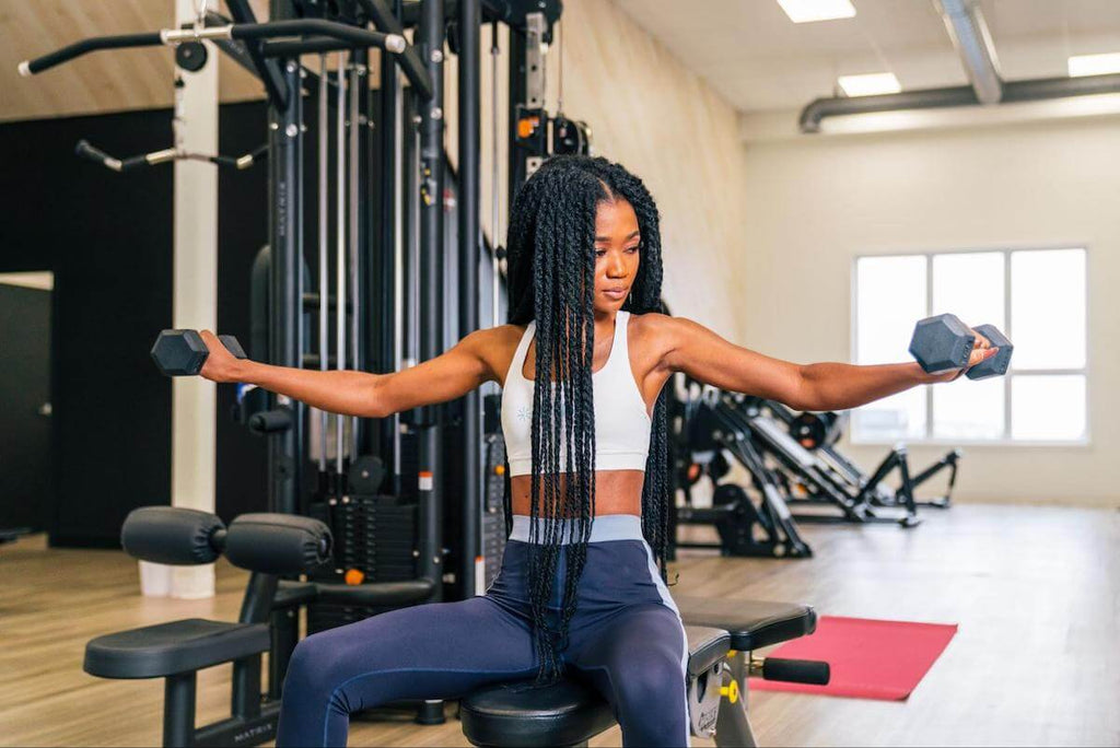 Shoulder workouts for women: woman doing a dumbbell lateral raise