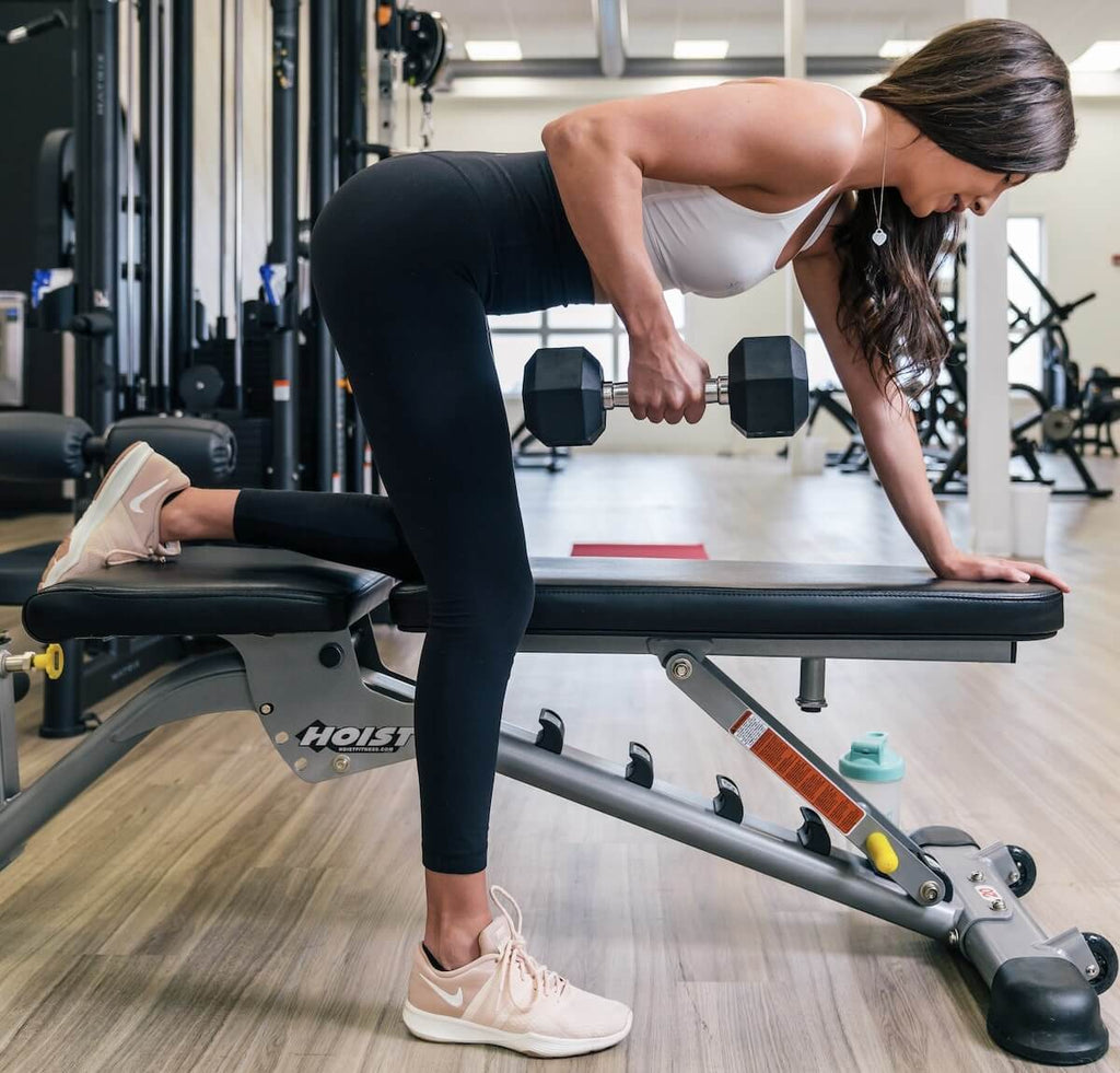 Glute activation exercises: woman doing dumbbell arm rows