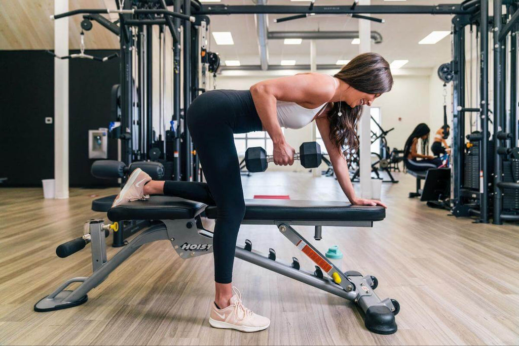 Core exercises for women: woman doing dumbbell rows
