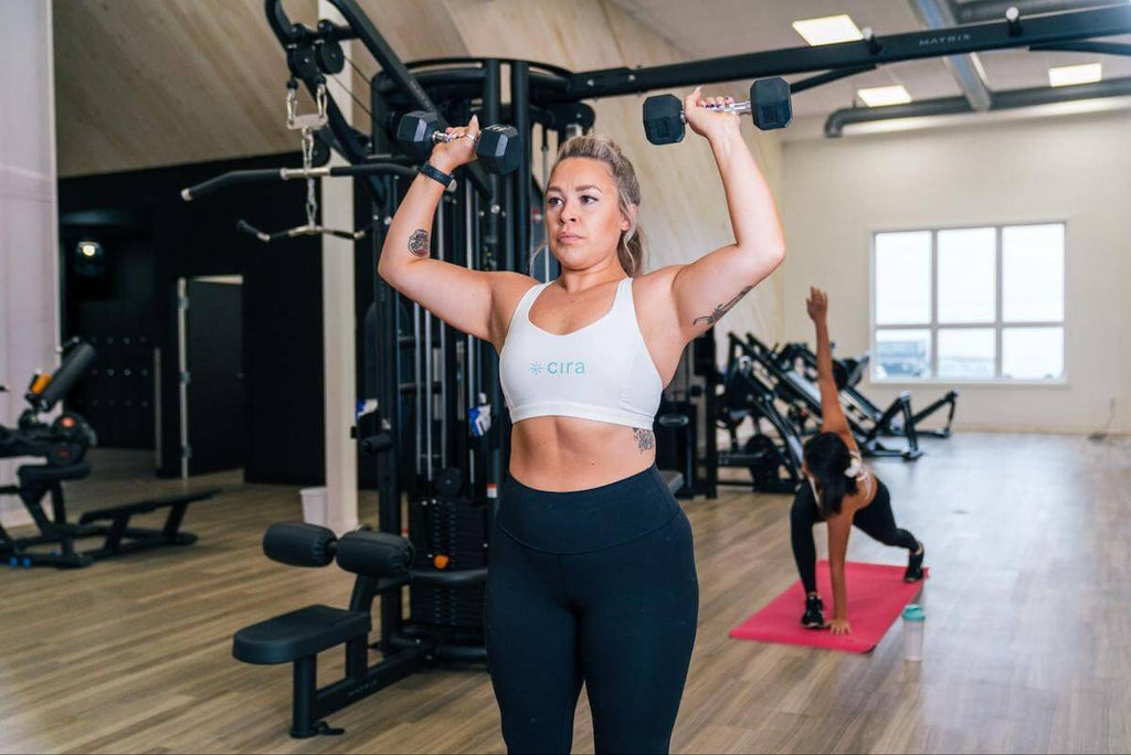 Full body workout for women: woman doing a shoulder press with dumbbells