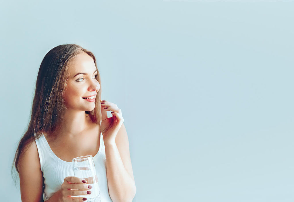 Woman holding a glass of water about to drink a pill