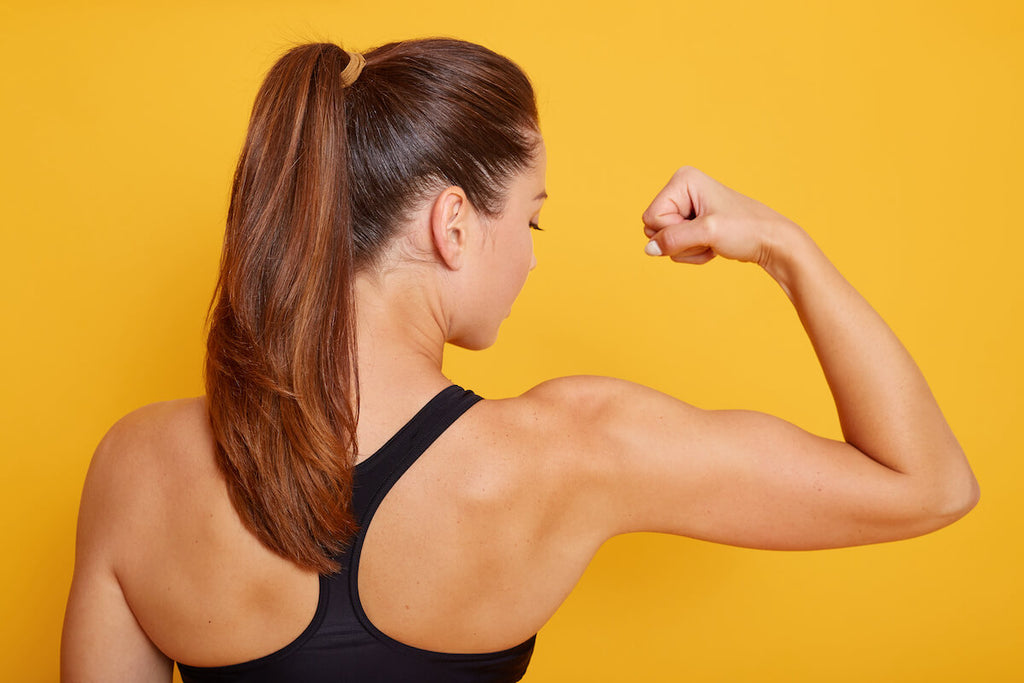 Shoulder workouts for women: woman flexing her bicep