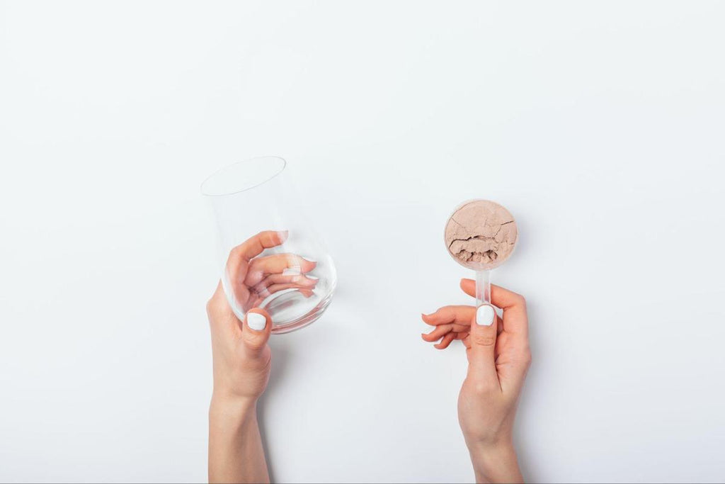 Protein powder for women: person holding a glass on one hand and a scoop of powder on the other
