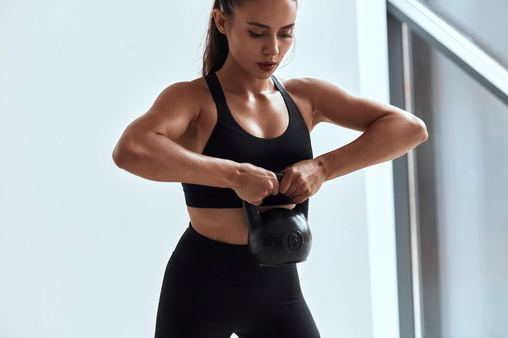Shoulder workouts for women: woman lifting a kettle ball using both hands