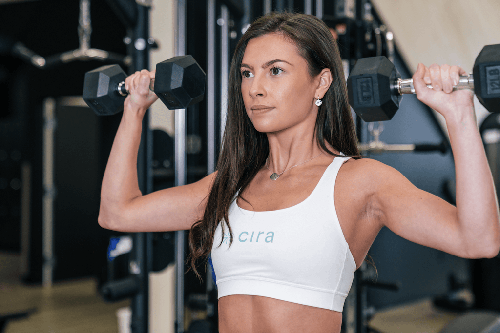 Upper body workout for women: woman doing shoulder press with dumbbells