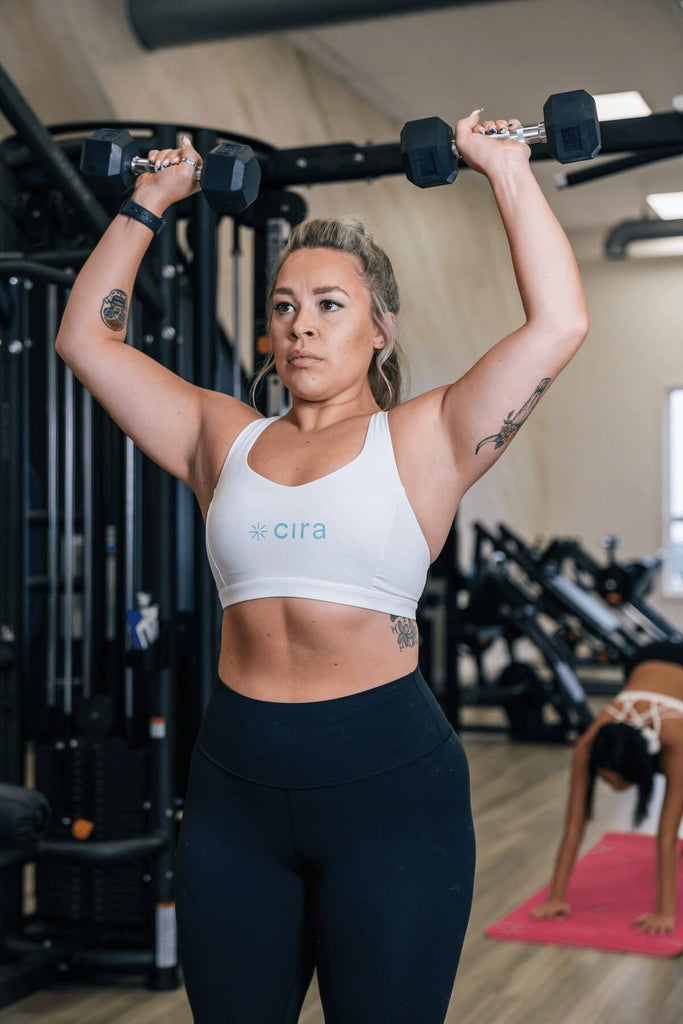 Woman doing a shoulder press with dumbbells