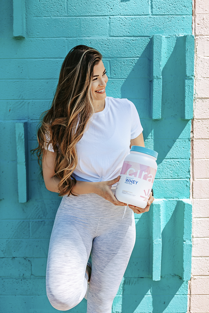 Woman standing by a bright teal wall holding a bottle of Cira Whey