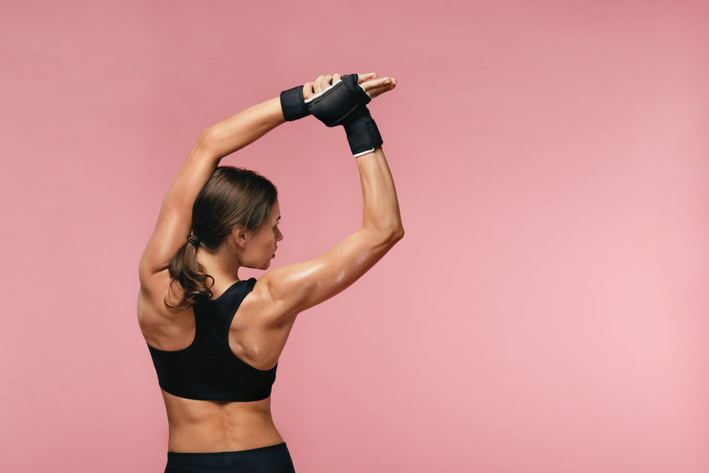 3 day split workout: woman stretching her back