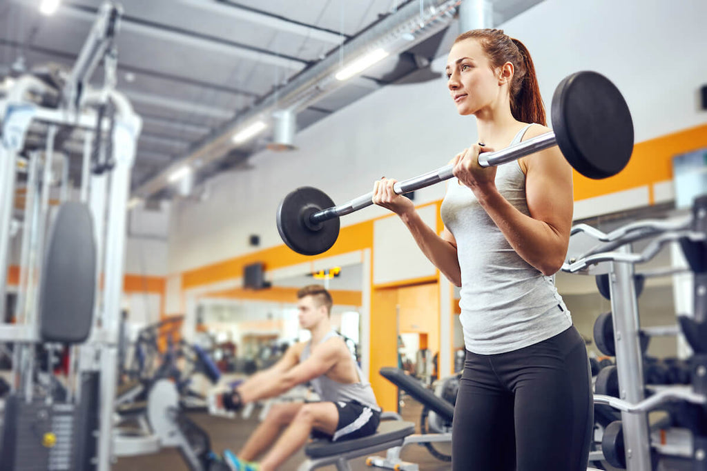 Full body workout for women: woman exercising with weights at the gym