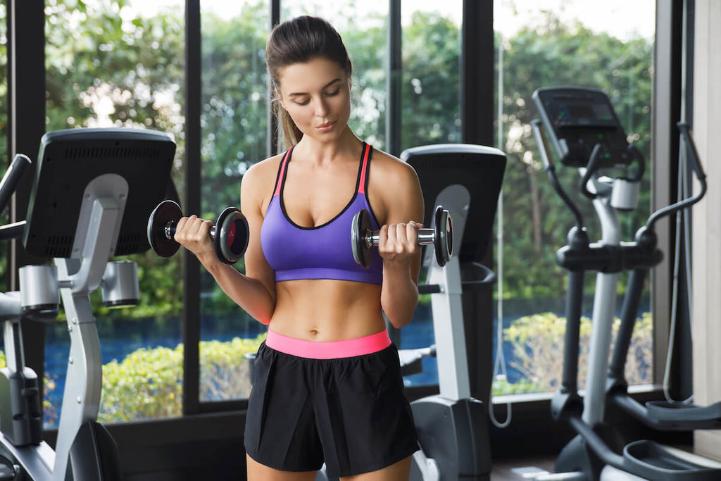 Upper body workout for women: woman doing bicep curls in the gym