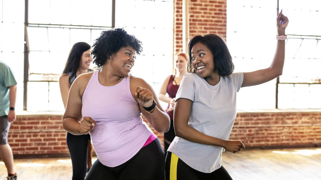 How to lose lower belly fat: women happily dancing during a Zumba class