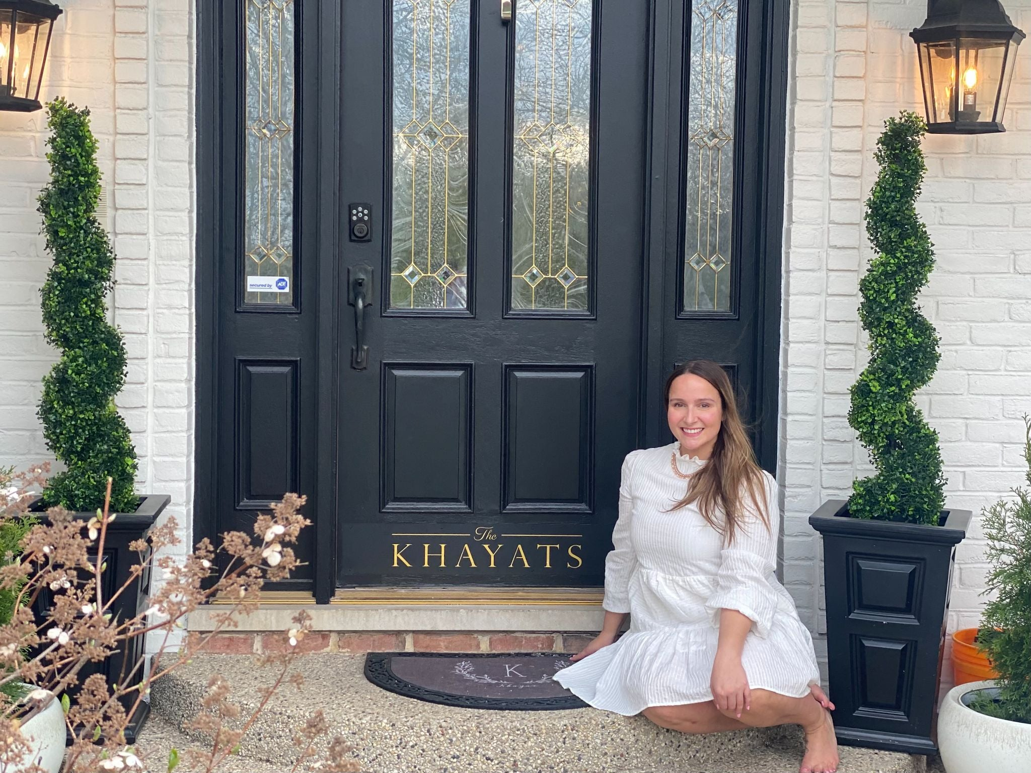 beautiful woman sitting front of an entrance door