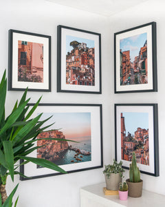 Soft pink and green-colored posters of Cinque Terre.