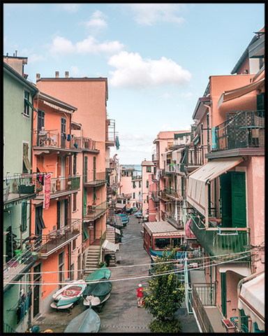 Manarola poster featuring a street in the town with pink and green-colored houses. Create an inspiring photo gallery with our Cinque Terre Collection.