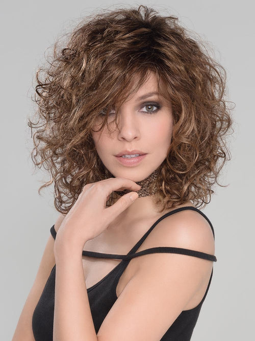 shoulder length style full of fun and bouncy curls all over. The density of this ready-to-wear synthetic hair mimics the natural look of curly hair and requires little to no customization or thinning